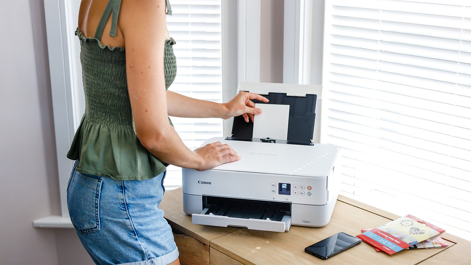 A woman loading photo paper into a white Canon PIXMA printer.